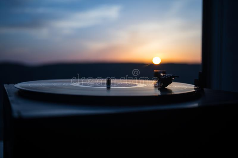 Turntable vinyl record player on the background of a sunset over the mountains. Sound technology for DJ to mix & play music. Black stock image