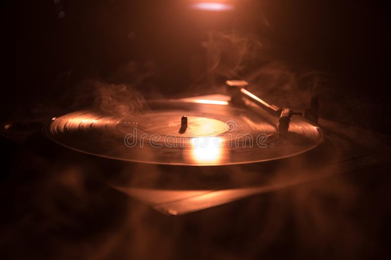 Turntable vinyl record player. Retro audio equipment for disc jockey. Sound technology for DJ to mix & play music. Vinyl record be. Ing played against burning stock photography