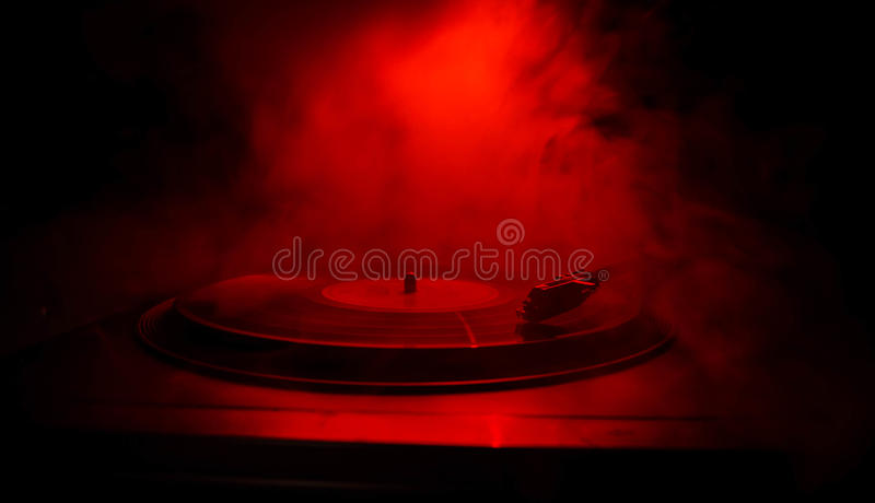Turntable vinyl record player. Retro audio equipment for disc jockey. Sound technology for DJ to mix & play music. Vinyl record be. Ing played against burning stock photos
