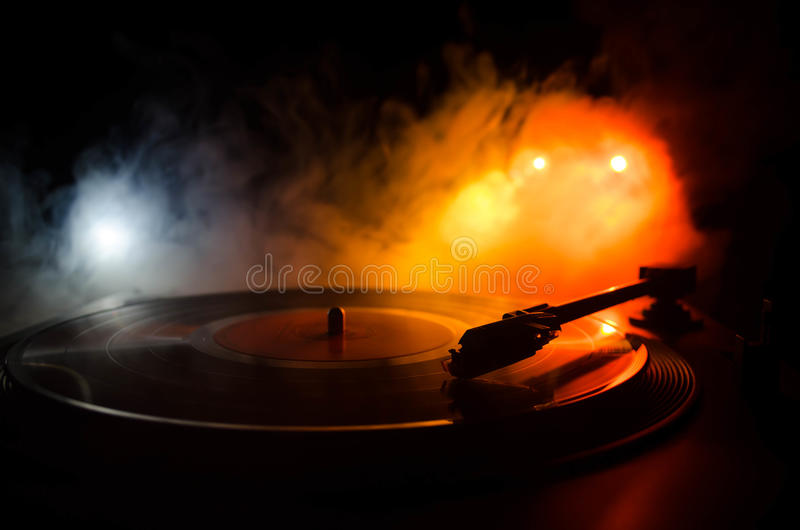 Turntable vinyl record player. Retro audio equipment for disc jockey. Sound technology for DJ to mix & play music. Vinyl record be. Ing played against burning stock photo