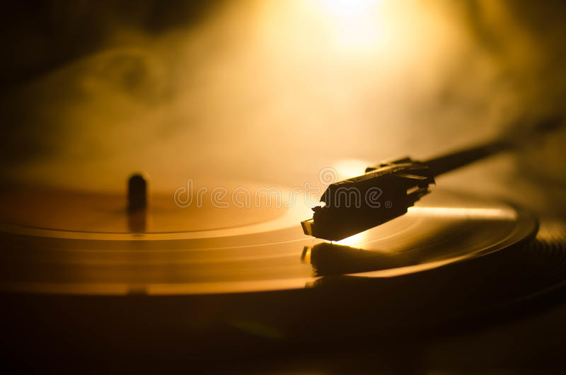 Turntable vinyl record player. Retro audio equipment for disc jockey. Sound technology for DJ to mix & play music. Vinyl record be. Ing played against burning stock images