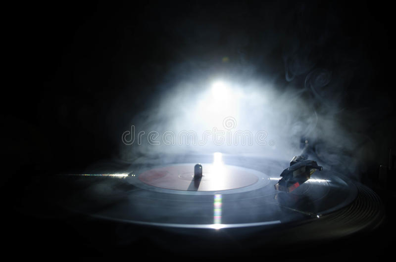 Turntable vinyl record player. Retro audio equipment for disc jockey. Sound technology for DJ to mix & play music. Vinyl record be. Ing played against burning stock image