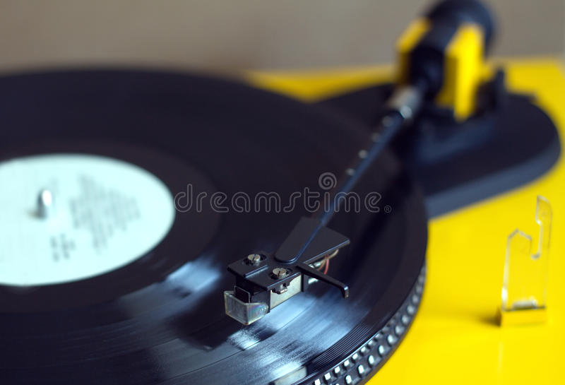 Turntable with vinyl record top view close up. Turntable in yellow case playing a vinyl record with white label. Horizontal photo top view closeup stock image