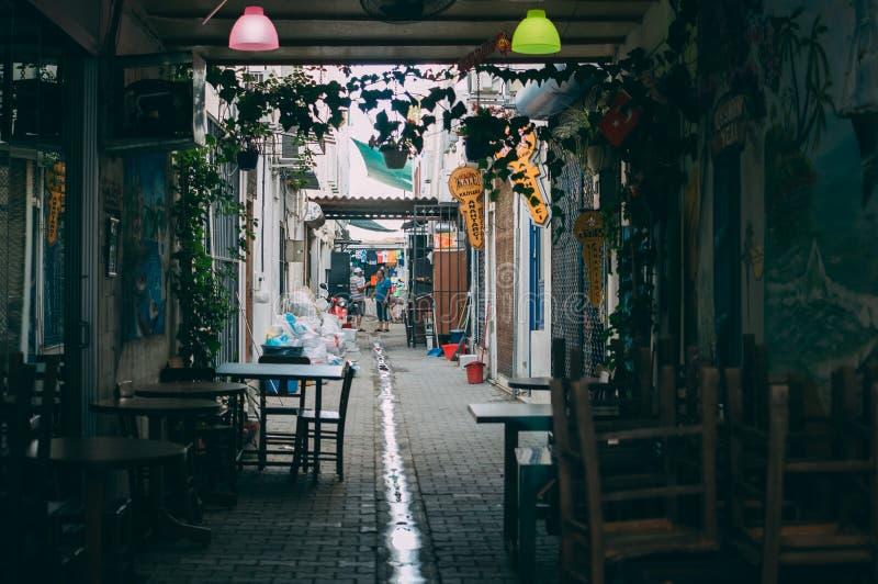 Turquía, Turgutreis, 10 de junio de 2018: Una pequeña calle cerca del bazar local, donde argumentan dos residentes locales, un pe imagen de archivo