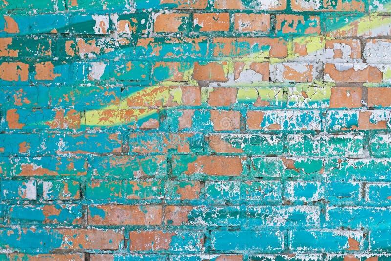 Turquesa colorida vieja y pintura amarilla con las grietas en la pared de ladrillo roja imagen de archivo