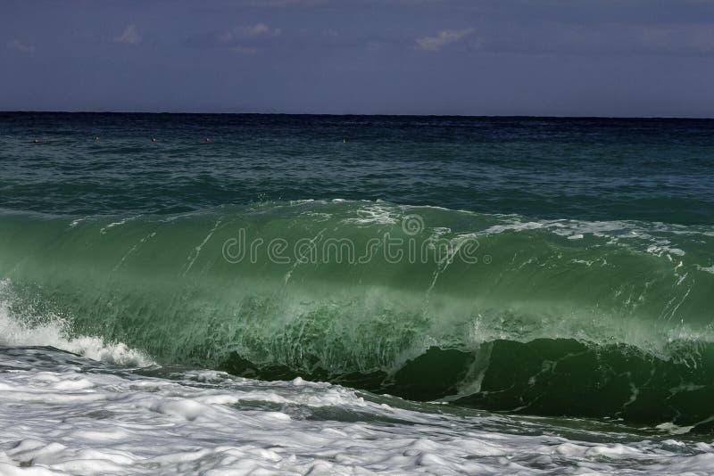 Turquesa majestuosa e inflamación de color verde oscuro que se estrellan en una playa en un día de verano del cielo azul en Sicil foto de archivo