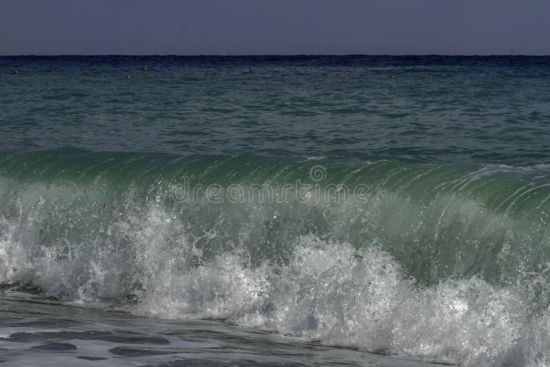 Turquesa majestuosa e inflamación verde que se estrellan en una playa en un día de verano del cielo azul en Sicilia imagen de archivo