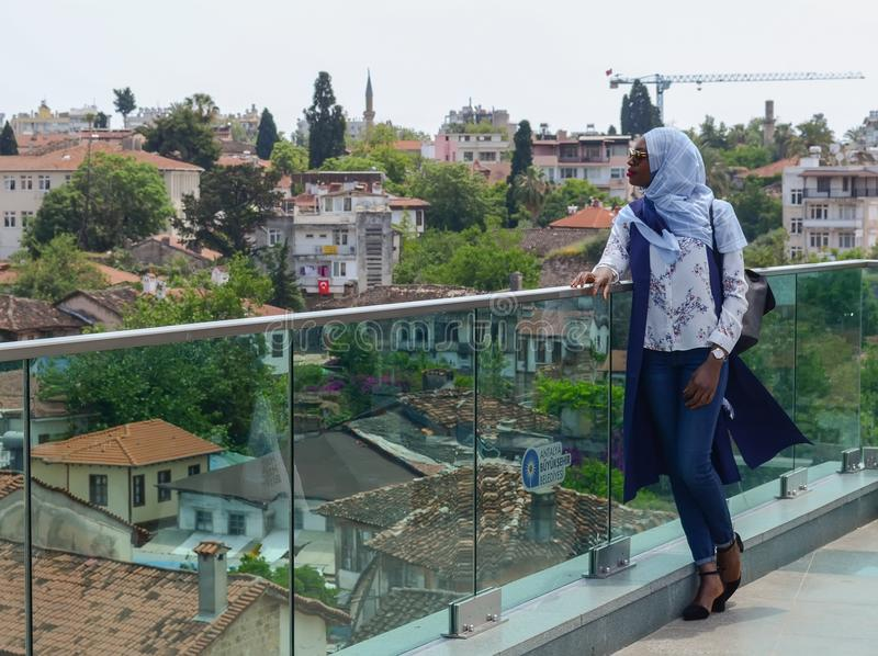 Turquia, Antalya, o 10 de maio de 2018 Jovem mulher africana na roupa, no lenço bonito e nos óculos de sol estando na plataforma  imagem de stock royalty free
