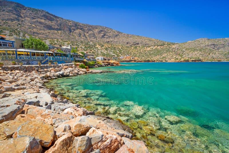 Turquise bevattnar av den Mirabello fjärden i den Plaka townen på Crete arkivbild