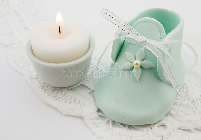 Turquoise baby fondant shoe with candle on white lace background stock photo