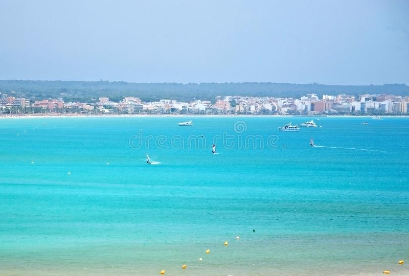 Turquoise bay with windsurfers. PALMA DE MALLORCA, SPAIN - JULY 14, 2012: Turquoise bay with windsurfers on a sunny summer day on July 14, 2012 in Mallorca royalty free stock photography