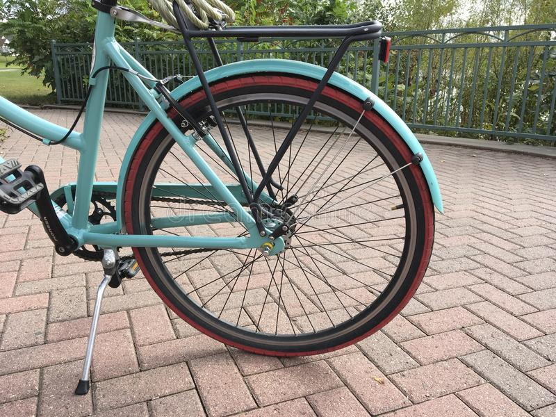 Rear Tire of Bike Paused at Park. Turquoise Bike paused at an overlook in a park in the summer. Terrace of Brick with a nearby railing royalty free stock image