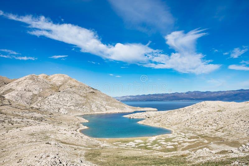 Turquoise blue bay surrounded by white karst rocky landscape and blue sky. Vela Luka near Baska, island of Krk, Croatia stock image