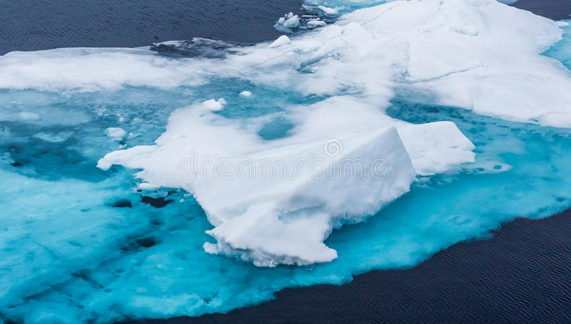 Turquoise blue glacier ice floats in the Arctic. Near Norway stock photo