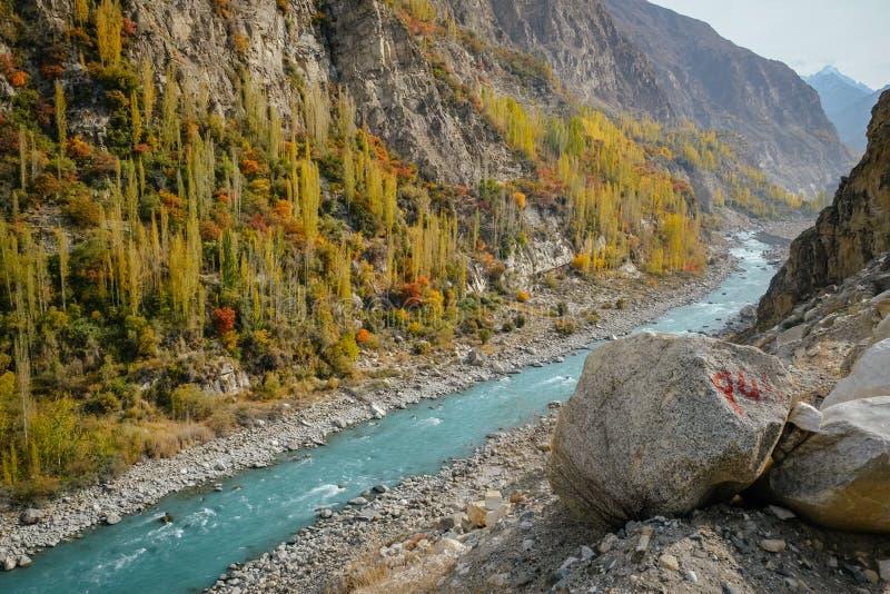 River flowing through Karakoram mountain range along Karakoram highway and colorful foliage in autumn royalty free stock photo