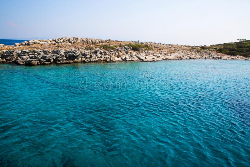 Turquoise crystal water of Meditteranean sea on bright shiny day. Bright crystal water of Meditteranean sea near Turkey and Greece borders stock image