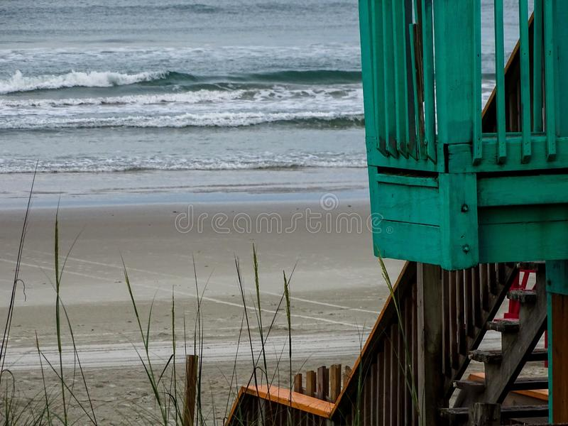Turquoise deck and steps of wood lead to beach. royalty free stock images