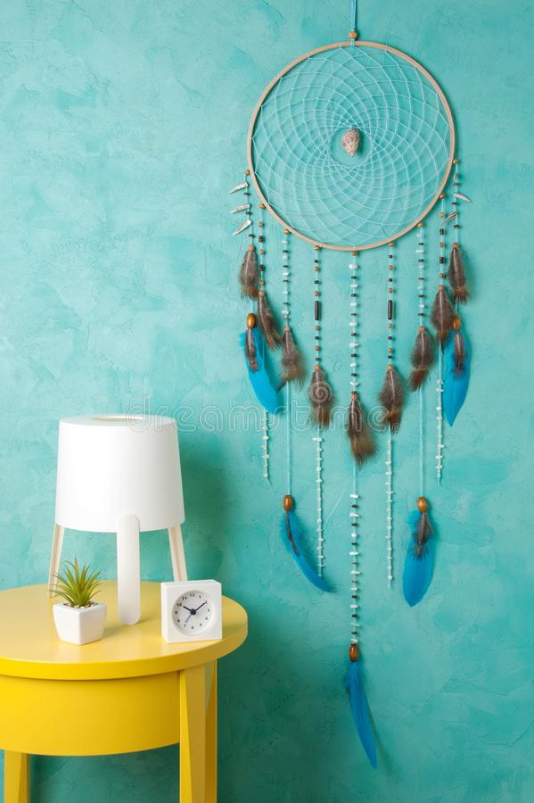Turquoise dream catcher. Yelioow nightstand , table lamp and alarm clock on aquamarine textured background. Texture of concrete,copy space for text royalty free stock photo