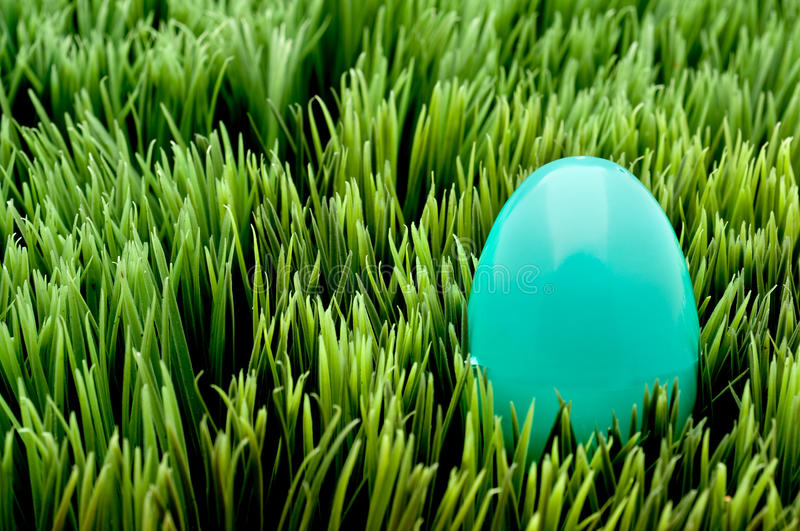 A turquoise Easter egg on green grass
