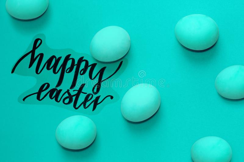 Turquoise and green easter eggs on background, black inscription happy Easter royalty free stock photo