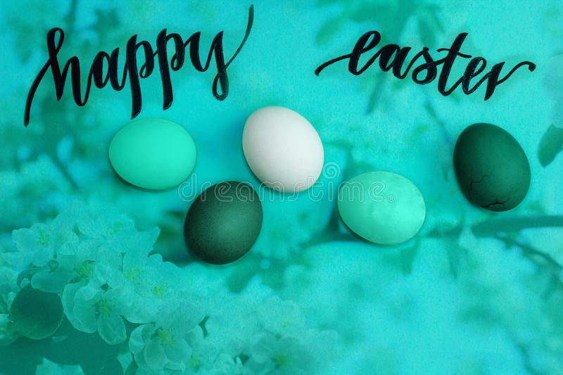 Multicolored easter eggs on turquoise background, black inscription Happy Easter royalty free stock image
