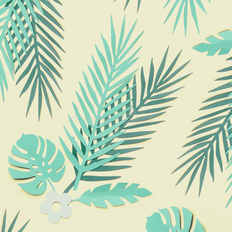 Turquoise green tropical leaves on pastel yellow background, top view, flat lay. Creative botanical layout stock image