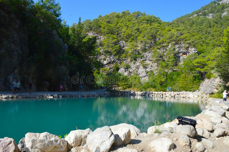 Turquoise lake on the background of mountains in the summer sunny day, Goynuk canyon near Kemer, Turkey. People walk by the lake and rest, the mountains are stock photo