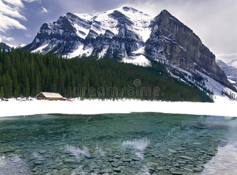 Turquoise Lake Louise Thawing in the Spring with Mountain Backdrop. Lake Louise melting in the seasonal sun royalty free stock photography
