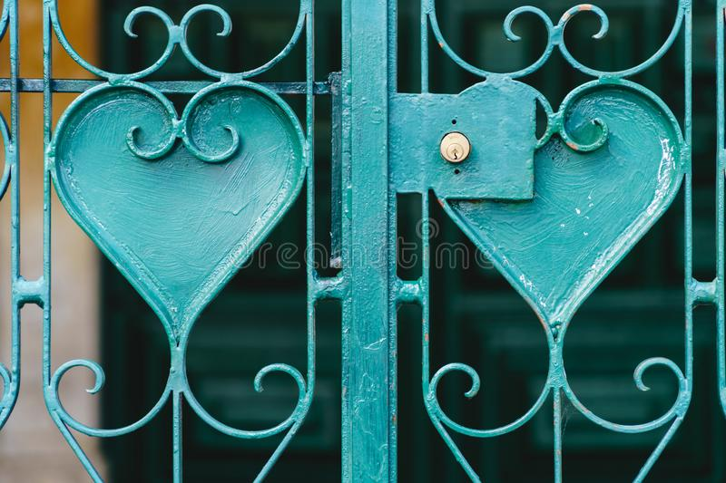 Turquoise metal grating with heart shaped ornaments - symbol of iron love. Close-up of a turquoise metal grating with heart shaped ornaments and a golden lock royalty free stock photo