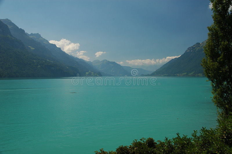 Turquoise mountain lake. Beautiful scenery of the mountain lake on a sunny day. Steep wooded hillsides on either side of the lake royalty free stock photos
