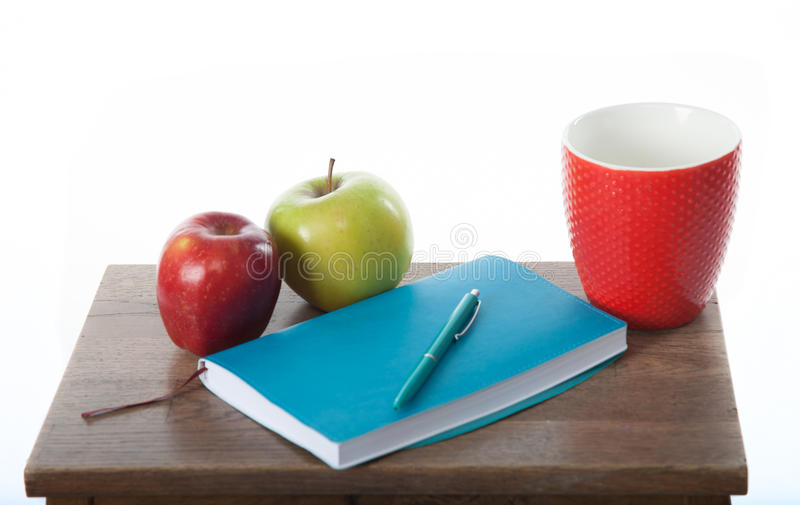 Turquoise notepad with pen, apples and cup. Work and study environment. royalty free stock photos
