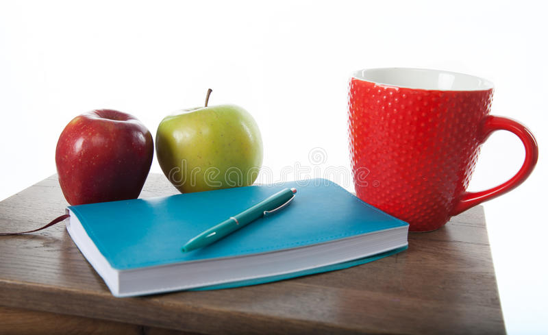 Turquoise notepad with pen, apples. Work and study environment. stock image