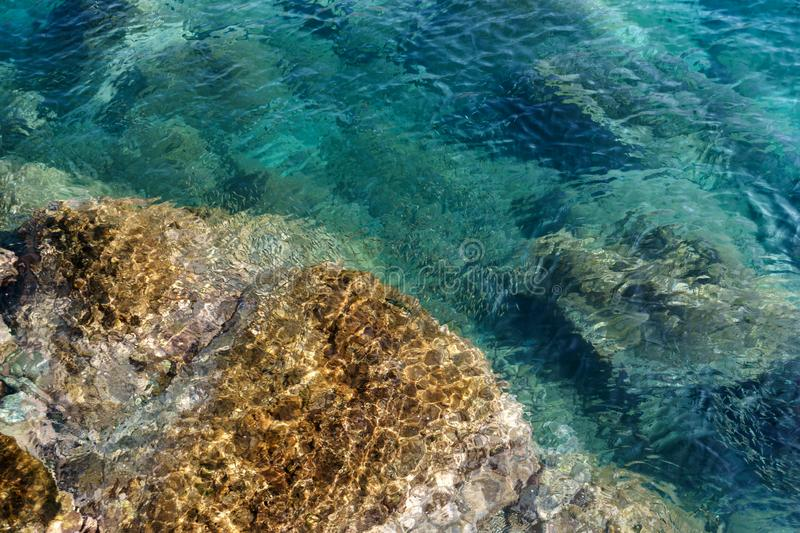 Turquoise ocean, sea waters with fish and rock cliffs.  stock photos