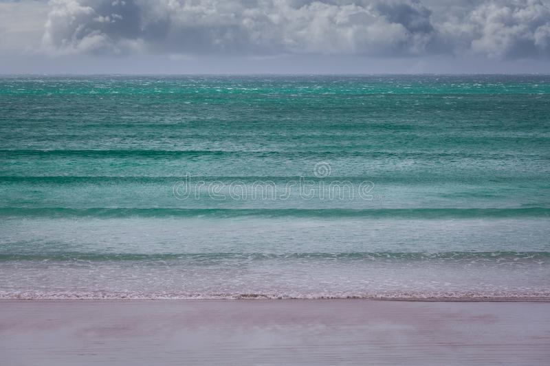 Turquoise ocean waves under stormy clouds - minimalist landscape. Turquoise ocean waves under stormy clouds - minimalist landscape stock photo