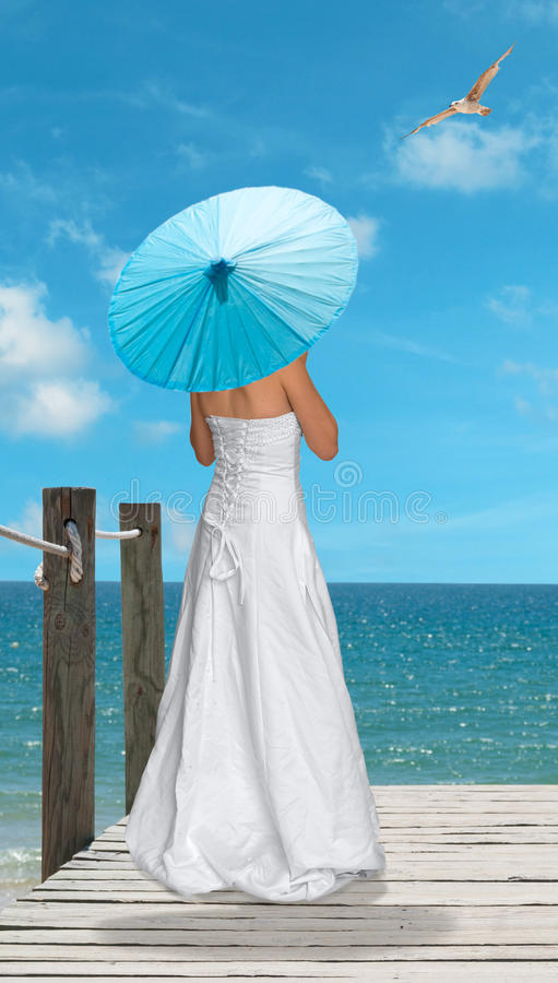 The Turquoise Parasol. Girl with turquoise blue parasol looking out across the ocean stock photos