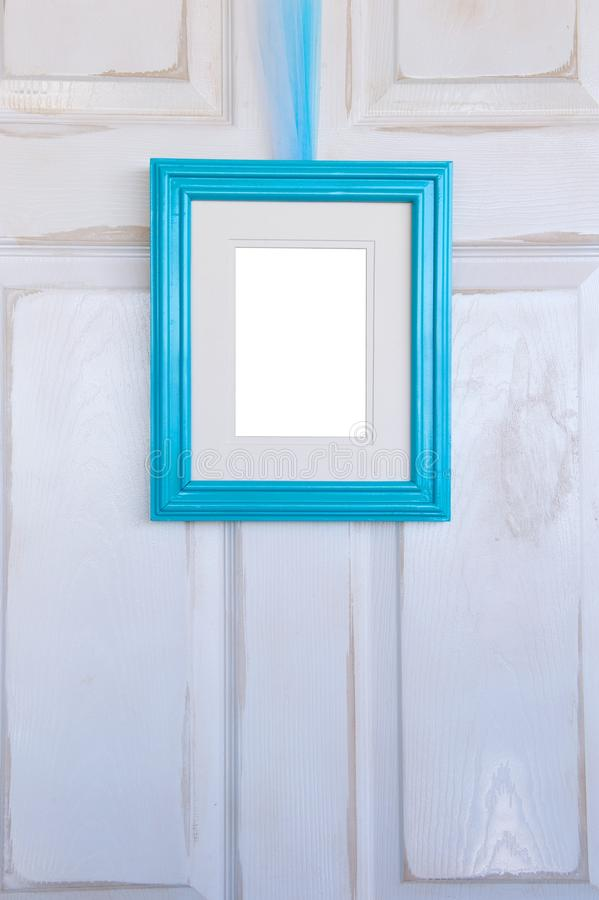 Turquoise Picture Frame Hanging on Distressed White Door royalty free stock photos