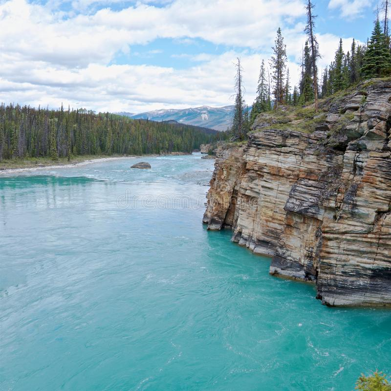 Turquoise river Athabasca flowing around picturesque rocks royalty free stock images