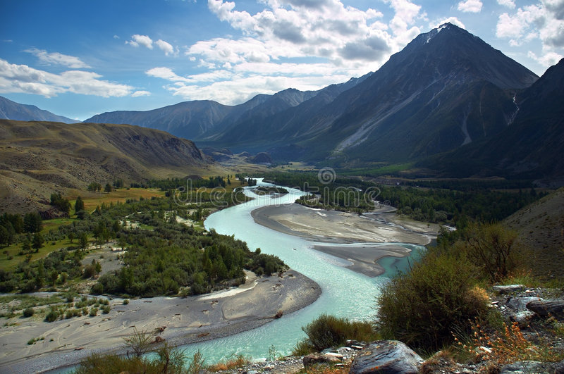 Turquoise river, mountains and skies stock photography
