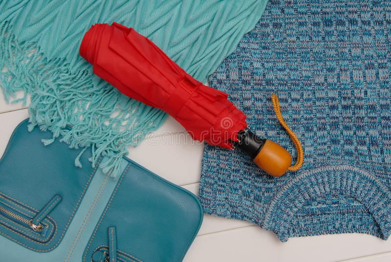 Turquoise scarf, red umbrella, blouse and bag stock image