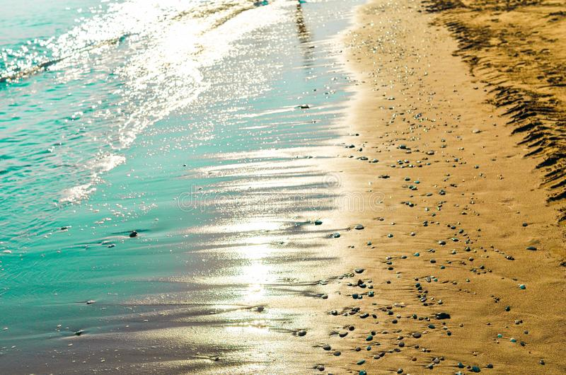 Turquoise sea and golden sand beach with small pebbles covered by sunlight backlight. Energy and balance concept. Turquoise sea and golden sand beach with small stock images