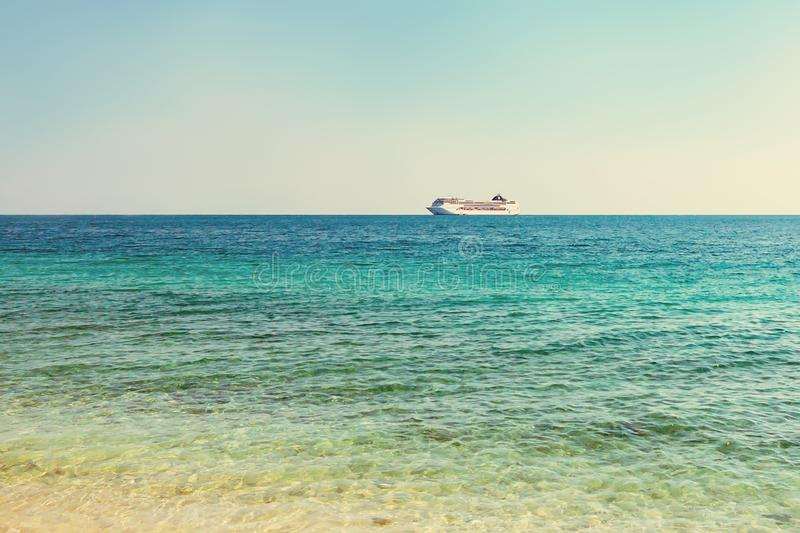 Turquoise sea with light ripples on the water and a large cruise liner on the horizon royalty free stock photography