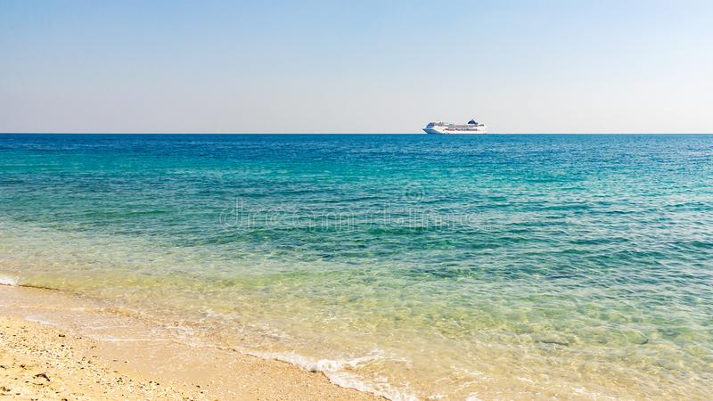 Turquoise sea with light ripples on the water and a large cruise liner on the horizon royalty free stock images