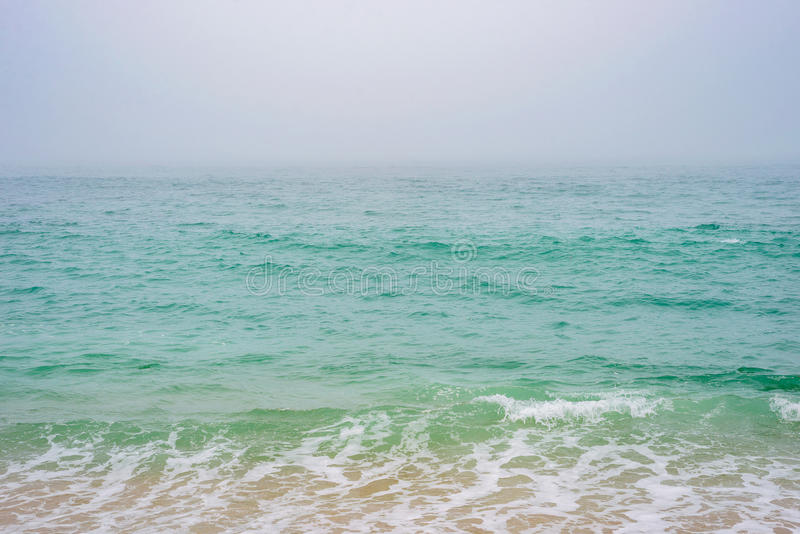 Turquoise sea ocean water horizon during fog mist storm for background texture stock photography