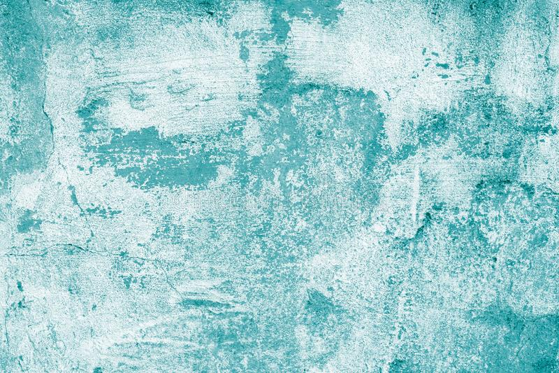 Turquoise shabby concrete wall with flaky plaster. Torn rough old texture. Vintage, cracked distressed background. Abstract green royalty free stock photo