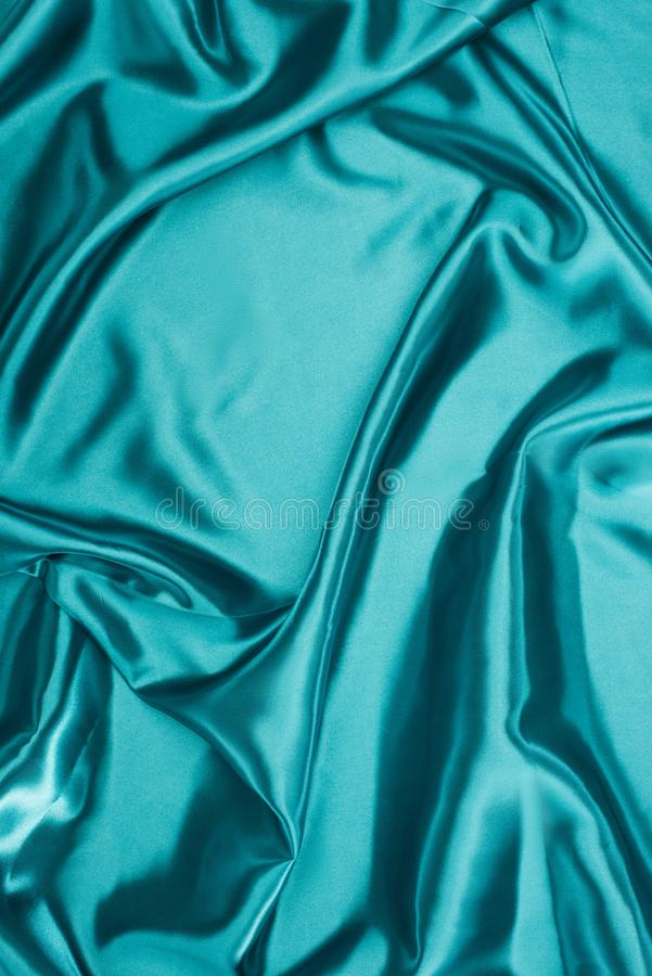 Turquoise shiny wavy satin. Fabric background royalty free stock photos