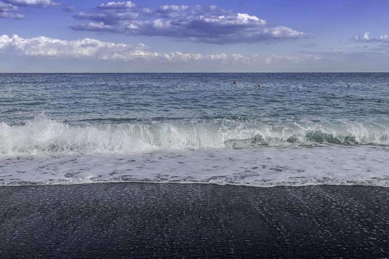 Turquoise Swells crashing into black pebbled beach on a blue sky summer day in Sicily. Turquoise Swells crashing into black pebbled beach Giardini di Naxos in royalty free stock photo