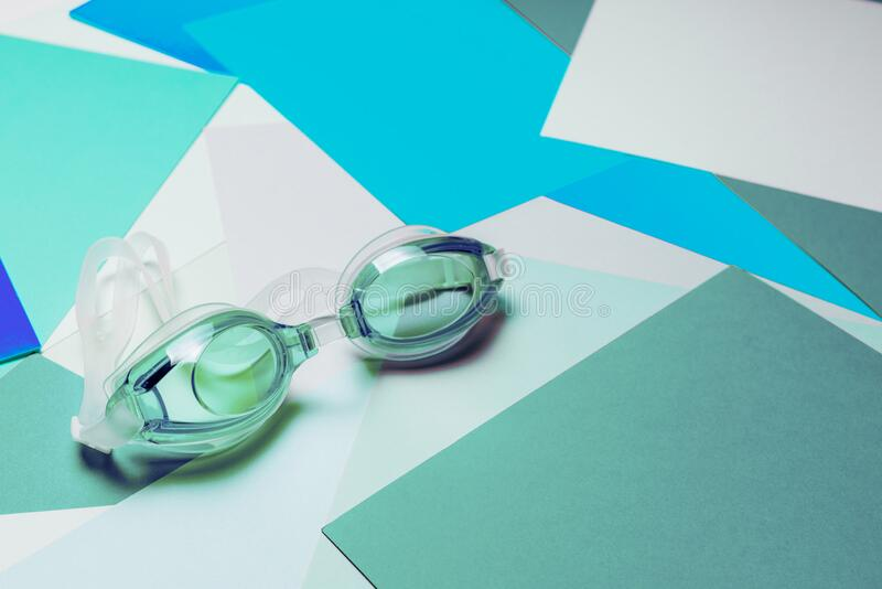 Turquoise swimming glasses, with rubber strap on multicolor geometric background royalty free stock photo