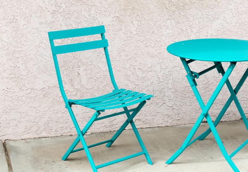Turquoise table and chair. On a city sidewalk royalty free stock images