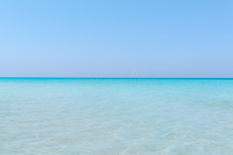 Turquoise tranquil ocean merging with clear beautiful sky at horizon line on sunny warm day. Amazing gorgeous natural background of turquoise tranquil ocean royalty free stock photo