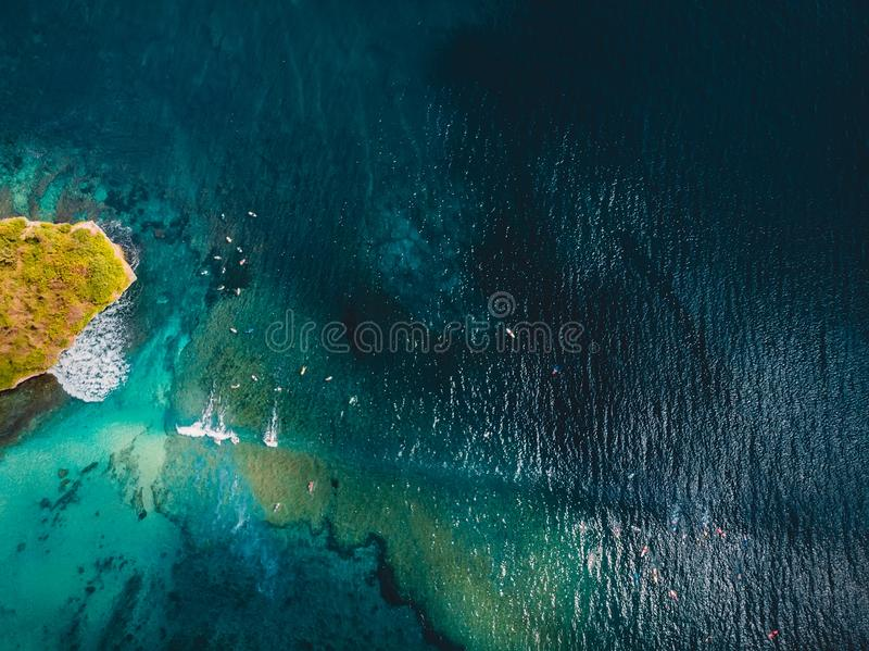 Turquoise tropical ocean with waves and surfer in Bali, aerial drone shot. Aerial view. royalty free stock photo